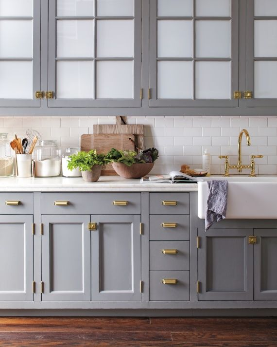 Brass hardware on grey kitchen cabinets. Image via Martha Stewart.