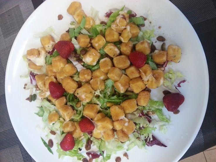 Mozzarelline fritte su un letto di insalata con pinoli, uvetta passa, fragole e una spruzzata di aceto di frutti di bosco
