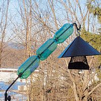 "Birds & Blooms reader Frances McLaughlin has this squirrel-busting solution: ""Squirrels can't get to my feeder anymore! I took three soda bottles and strung them through an extending rod. Then I bolted the rod to our porch rail. Now I can easily swing the rods to the rail when I fill the feeders, and the setup keeps squirrels away at the same time."""