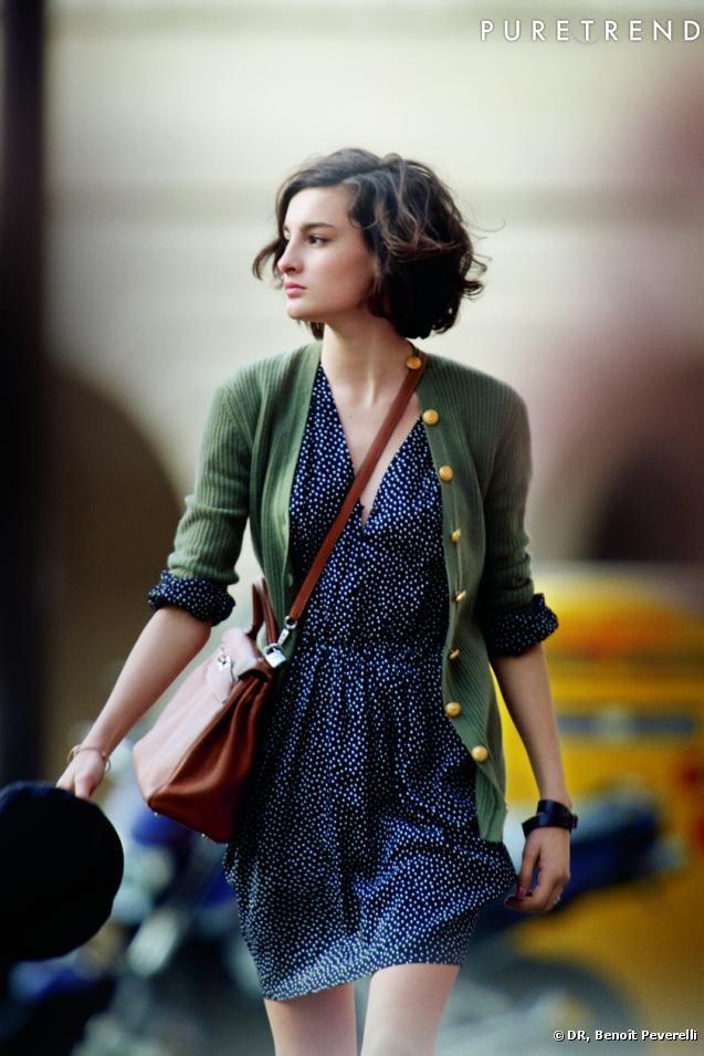 La Parisienne, incarnée par Nine d'Urso, sait aussi mixer avec désinvolture une robe fluide à pois avec un long cardigan à boutons dorés et un sac en bandoulière.
