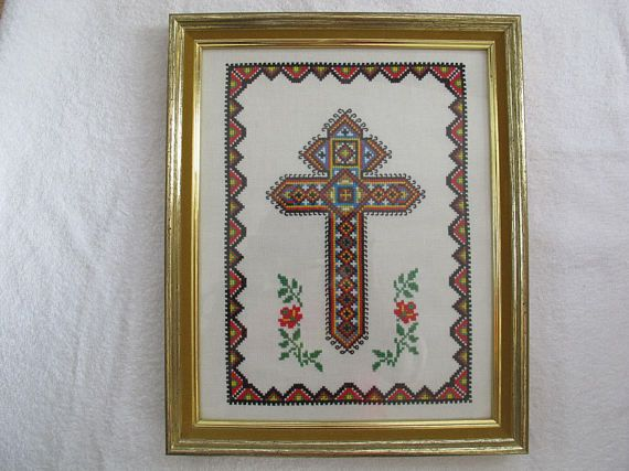 Striking Ukrainian cross stitch framed picture of a cross. Nicely worked in primary colours. Nicely framed in a gold frame with velvet edging. Overall size is 16 by 13 inches. Excellent condition.  This piece may require an oversize box - shipping will depend on the shipping distance as