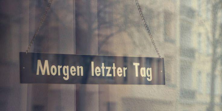 """Ein Schild mit der Aufschrift """"Morgen letzter Tag"""" hängt in einer Tür"""