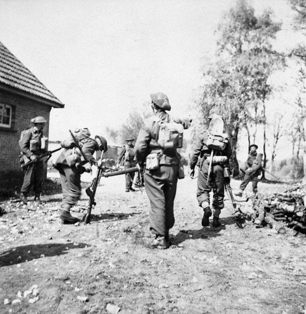 """Infantrymen of """"D"""" Company, Royal Regiment of Canada, examine equipment taken from surrendering German soldiers during the advance from Hatten to Dingstede, Germany, 24 April 1945."""