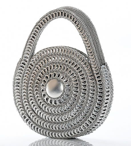 """Small Spiral  Circular hand-held purse   •Hand crocheted in a swirl pattern with over 600 recycled pop tops   •The center hub is a recycled aluminum can bottom   •Compact and cute design makes it a magnet for attention   •Fully lined with mettalic silver satin zipper.   Zipper closure   •Size: 9.5"""" diameter. 1.5"""" width, 3.5"""" handle   •Color: Metallic silver only     $135.00"""