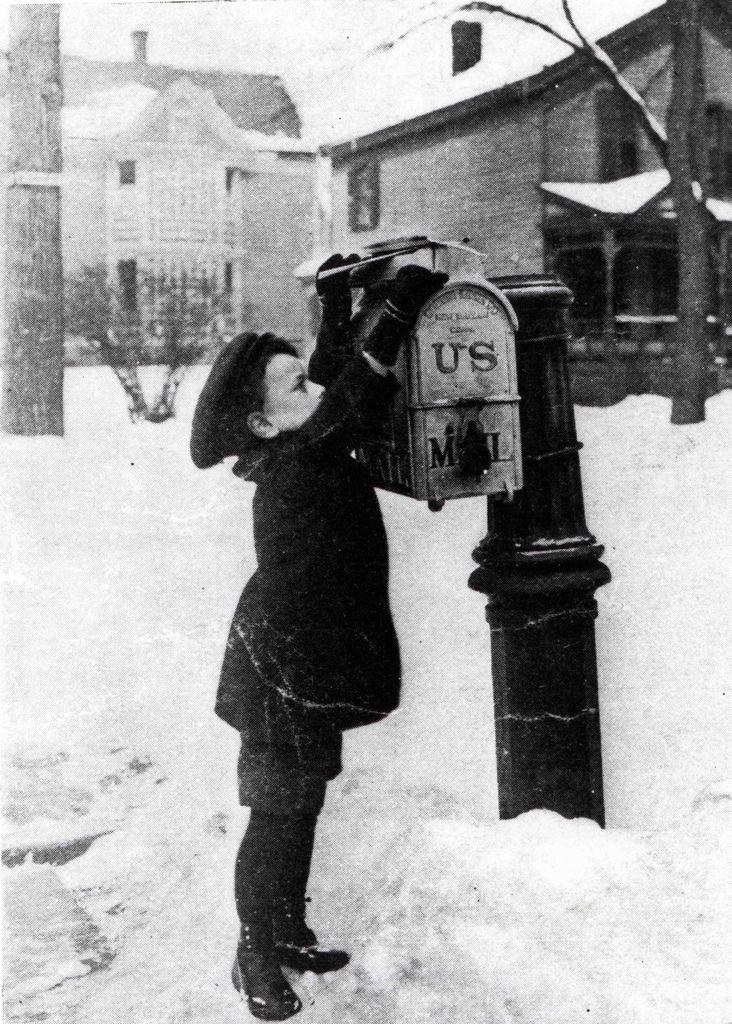 Young boy does his best to put his letters into a Doremus-style mailbox 1880