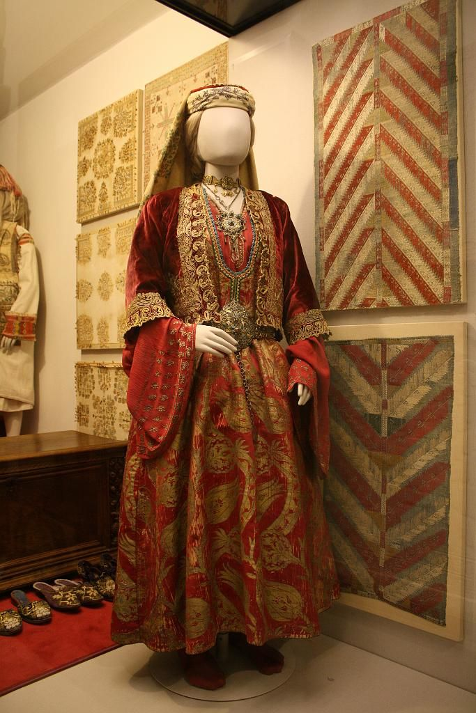 Costume of Thasos / Θάσος, dress made with 16-17th century bursa gold-woven fabric. Dated 1775. Benaki Museum, Athens, Greece {{slideshow}} [http://www.thassos-island.gr/el/%CF%80%CE%BF%CE%BB%CE%B9%CF%84%CE%B9%CF%83%CE%BC%CF%8C%CF%821/item/536-%CE%B7-%CF%80%CE%B1%CF%81%CE%B1%CE%B4%CE%BF%CF%83%CE%B9%CE%B1%CE%BA%CE%AE-%CF%86%CE%BF%CF%81%CE%B5%CF%83%CE%B9%CE%AC-%CF%84%CE%B7%CF%82-%CE%B8%CE%AC%CF%83%CE%BF%CF%85.html] [http://www.lifo.gr/uploads/image/391574/benaki2.jpg]