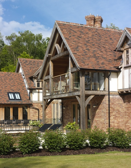 External view of oak framed covered balcony. Note how the hand made clay tiles give pleasant undulation to the roof line.