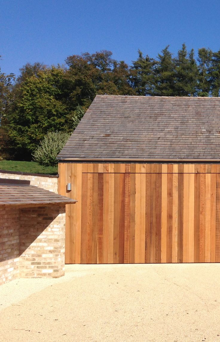 McLean Quinlan - The Stables. Cedar cladding with Shingle roof. Brickwork wood store + concealed garage door