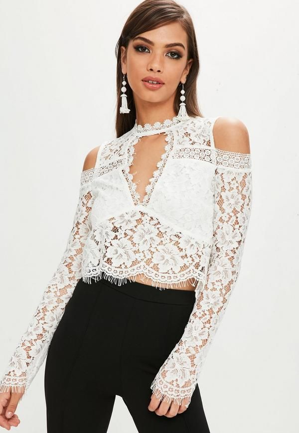 white top in a cropped style, cold shoulder and floral lace overlay.