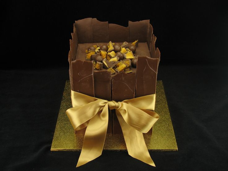 A chocolate mudcake with 4 layers of cake separated by milk chocolate ganache and chopped Crunchie bars. The sides of the cake are large shards of dark chocolate. On top there are more Crunchie bar pieces and some Maltesers for decoration.
