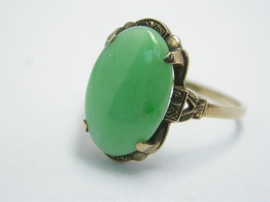 One 10 karat yellow gold vintage ring. One oval cabochon jadeite jade (5.75 carats: natural light green colour with minor zones of brighter colours).