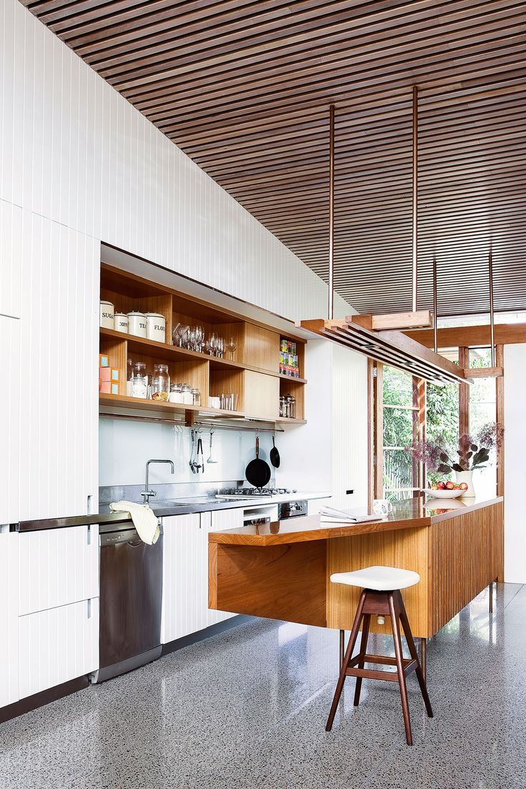 Kitchen: blackbutt timber ceiling battens, white cabinets with vertical panelling, glass splashback, grey polished concrete floor, timber linear pendant light, blackbutt island bench