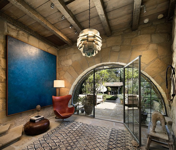 Ellen DeGeneres and Portia de Rossi's Romantic Santa Barbara Villa | Steps up from the living area, a spacious vestibule introduces the delightful bedroom wing, where the timeless style of stone walls and wood-beamed ceilings continues. A striking arched iron window opens to a sunny courtyard.
