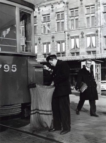 Postbode/medewerker posterijen leegt bij het station in Amsterdam een brievenbus die aan de achterkant van een tram (lijn 2) is bevestigd. Amsterdam, [1958].