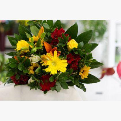 Μπουκέτο με κόκκινες ζέρμπερες, κίτρινες ζέρμπερες, πορτοκαλί λίλιουμ, λευκά τριαντάφυλλα, κίτρινα τριαντάφυλλα, χρυσάνθεμα και πρασινάδα.