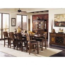 "The Larkspur Dining Room Collection is crafted in a rustic casual style and features Pine Solids and Birch Veneers with a Burnished Caramel finish. This 9 piece set contains the Larkspur high dining table, with two 14"" leaves and two 15"" hidden storage trays for flatware, and 8 upholstered high dining chairs. Table Size: 36W x 76-90-104D x 36H"