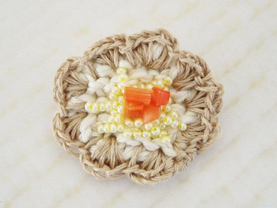One of a kind handmade brooch with beads, handknitted with a crochet edging.