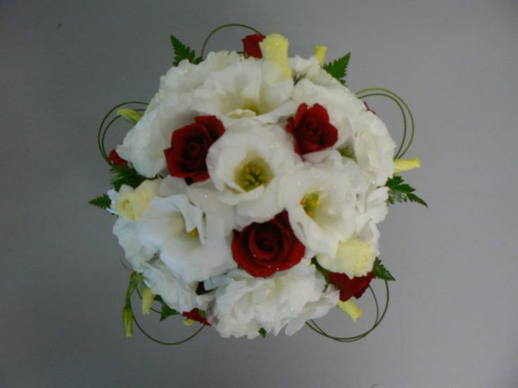 Mostly white lisianthus bouquet with red roses mixed amongst, spear grass & camelia foliage frame this simple creation