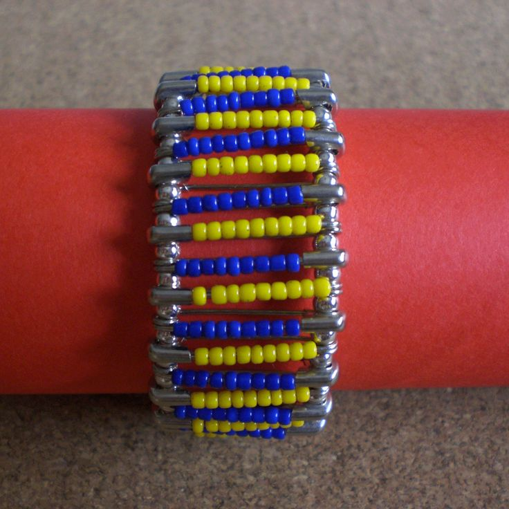 Bracelet made using safety pins with blue and yellow plastic beads. Connected with silver round beads.