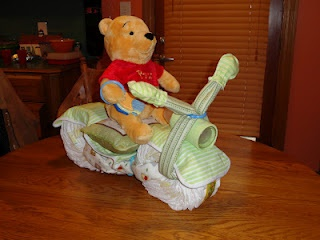 Here's the diaper cycle I did as an alternative to the diaper cake for my bonus-sister's baby shower. The nursery theme was Winnie the Pooh which was easy to theme the cycle around. I merged two designs when creating this one. You can see the instructions for each design from this post. It was a big hit at the shower!