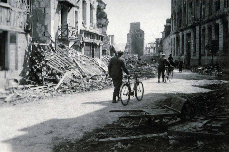 Rue de Caen, Lisieux après les bombardements de juin 1944. En arrière-plan façade peinte : Lion Noir, réclame de cirage.