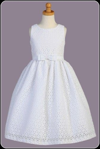 This lovely white cotton Communion dress features beautiful embroidered and eyelet flowers throughout, sleeveless bodice, center bow at the waist with a tie back satin sash and t-length skirt.