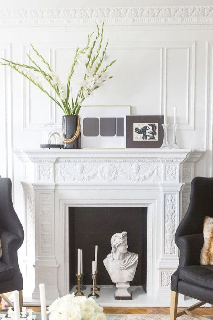 Classic living room with crown molding, a white fireplace, and black chairs.