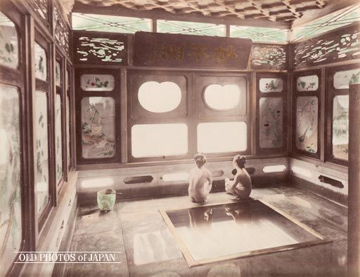 1880's. Two Women In Bathroom. Two women are squatting next to a bath in a beautiful wooden bathroom in Hakone, a famous onsen resort. Two other popular resorts were Ikaho and Atami. The windows feature artwork and the panels above them contain gorgeous displays of woodwork. A wooden ladle rests on the marble water pail in the left corner.
