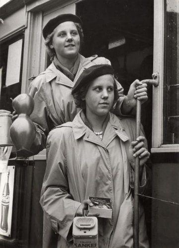 Tweelingen. Meisjes tweeling met identieke regenjas en alpino mutsen/petten,   collecteren voor het KWF voor de Kankerbestrijding. Na het offeren in de   collectebus ontvangt men een speldje/vlaggetje. Plaats [vermoedelijk]    Amsterdam jaren '60-'70.
