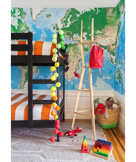 With clever storage and design ideas, this boys' room combines flair with functionality. Bold, saturated colors in the bedding and giant, wall-size map add style, while ample shelving gives the space structure. The super-high shelves are a perfect spot to display a globe collection or other items that aren't often in play, and the others—plus the window sill!—keep the rest of the toys neatly contained.