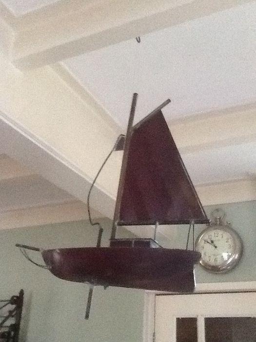 Koperen zeilboot om te hangen staand of als windvaan voor op het dak  Heel apart deze koperen zeilboot die u op verschillende wijzen kunt etaleren.Hij kan gebruikt worden als windvaan of als buitendecoratie hij heeft een buis aan de kiel. Ook mooi gewoon hangend in huis zwevend aan het plafond als bijzondere eyecatcher. (dik vislijn doet de truc) Ook kan hij staand geëtaleerd worden u zult dan zelf een klos met buis een zware fles of iets dergelijks moeten verzorgen om hem in te plaatsen.De…