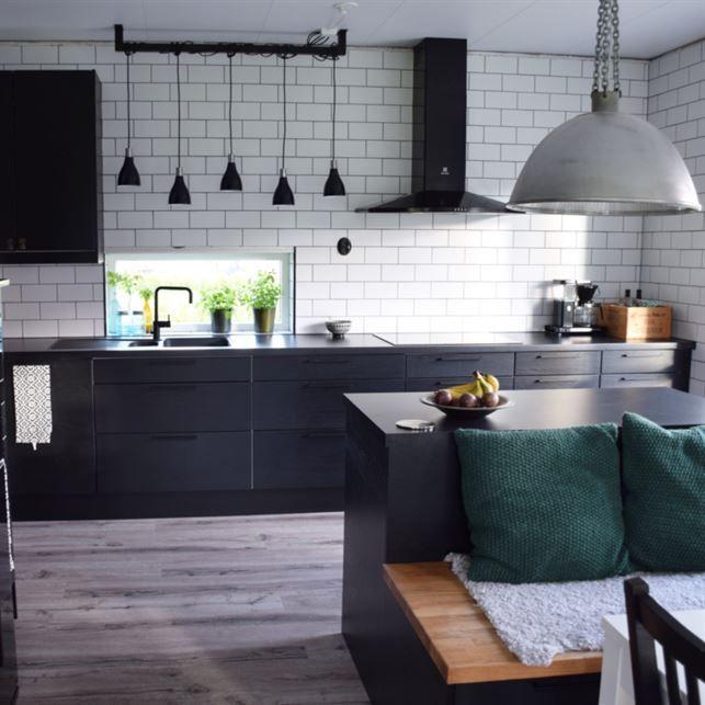 Svart kök. Köket är från Epoq. De fem lamporna över diskbänken kommer från Clas Ohlson och den stora över köksön är en omgjord industrilampa.