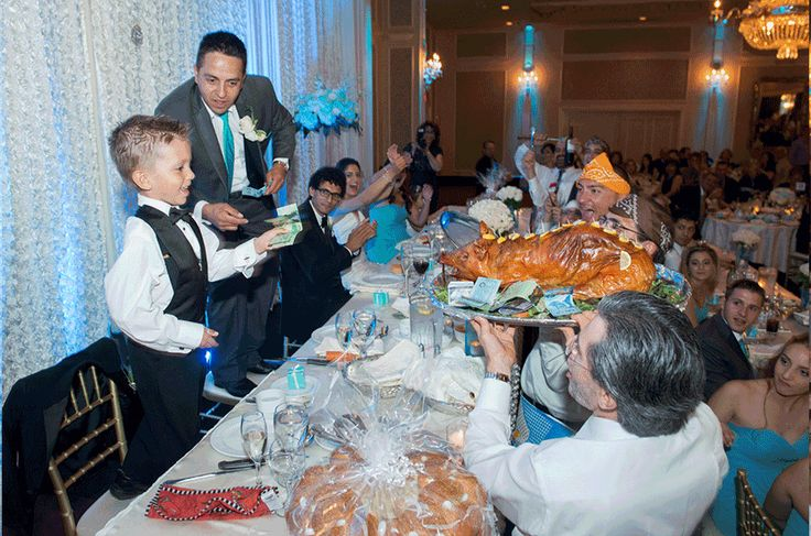 Crystal Fountain Wedding Reception, Ring Boy pays money for pig during the pig dance gif. Groomsman cheers.