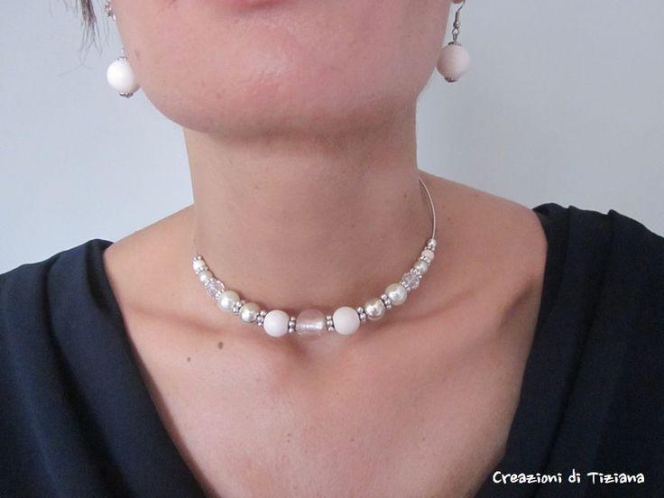 Collana a girocollo realizzata con pietre a sfera liscia di diverse misure di colore bianco panna, bianco trasparente e di color argento.