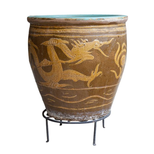 This Asian planter features a celadon glaze on the interior and rim, with a carved, gold-glazed dragon circling the brown body. Although clearly a fabulous planter for a large plant it also can stand alone as a decorative accessory. It also would be great for firewood.