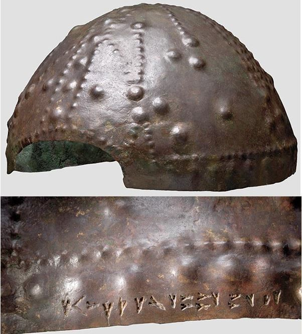 Iranian helmet with inscription, 1st half of the 1st millennium B.C. A bronze hemispherical skull with a rectangular face cutout. Rich decoration in the form of strips of bosses, and an anthropomorphic image on the forehead with bent arms raised upwards (prayer posture). In the neck area deeply incised cuneiform script (Elamite?) cartouches, as yet unreadable, next to two bronze rivets, possibly for the neck guard, 14.5 cm high. Private collection, from Hermann Historica auction