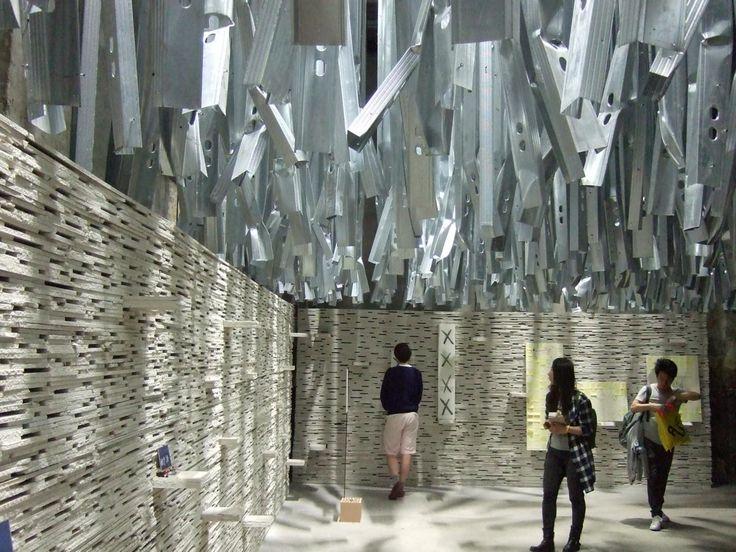 Recycling: Gebogene Aluprofile, die von der Decke hängen und eine Wand aus Gipskartonplatten – für die Hauptausstellung der diesjährigen Architekturbiennale in Venedig wurden 100 Tonnen Material der Kunstbiennale vom letzten Jahr wieder verwendet. Auch das meint einen bewussten Umgang mit Ressourcen.