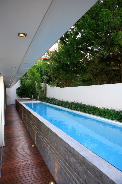 . I'd love to know more of the construction details. Is this a continuous poured enclosure? Build up from block? There are so few examples of above ground lap pools and this one is killer! SO pretty, such clean lines, so compact. Please provide more details... Lap pool- stone veneer wall- floor and ceiling lights... Above ground pool