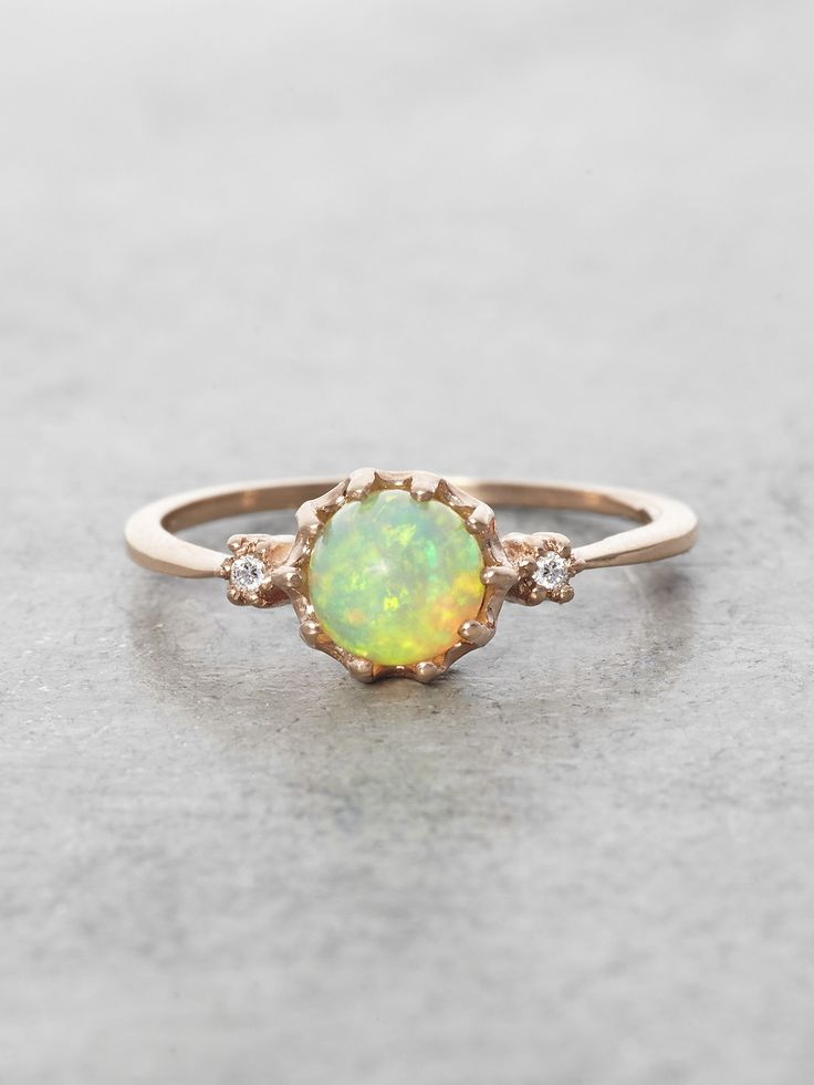 A glowing orb of fiery natural Opal is flanked by 2 brilliant cut Diamonds and grasped in a delicate setting of Solid 14K Gold (Shown in Rose Gold). Opal Ball measures approximately 6 mm. Handcrafted