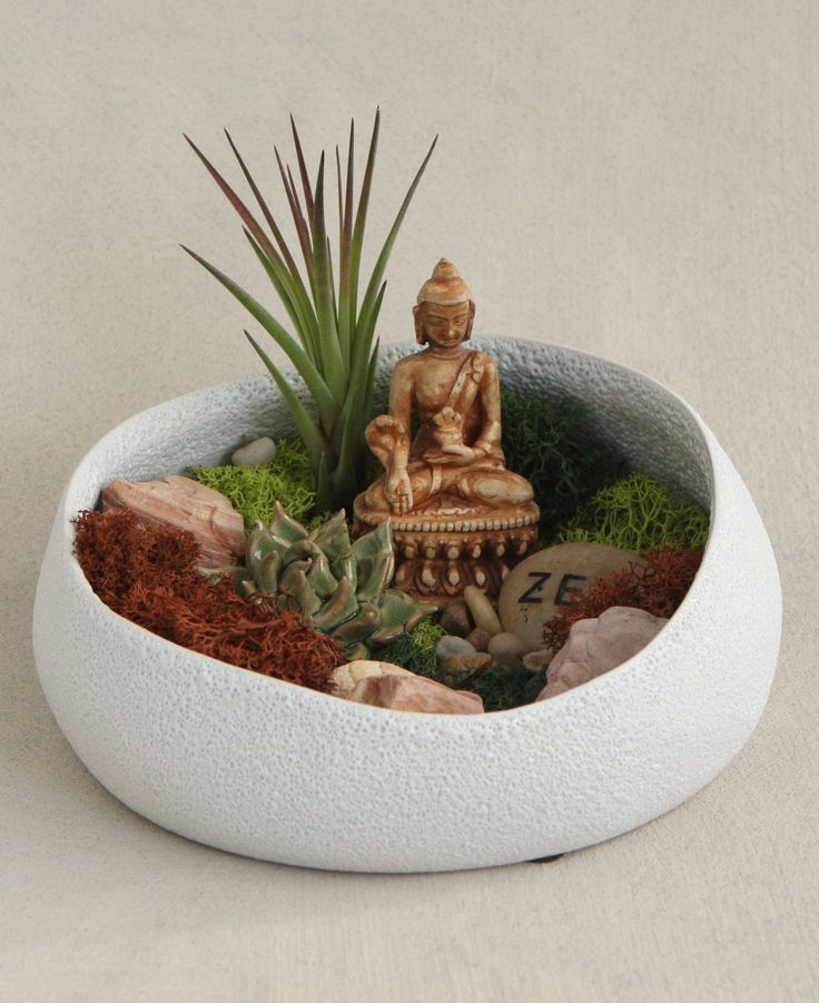 Eclectic terrarium with colorful moss and Buddha statue creates a unique display that emanates positive vibes.