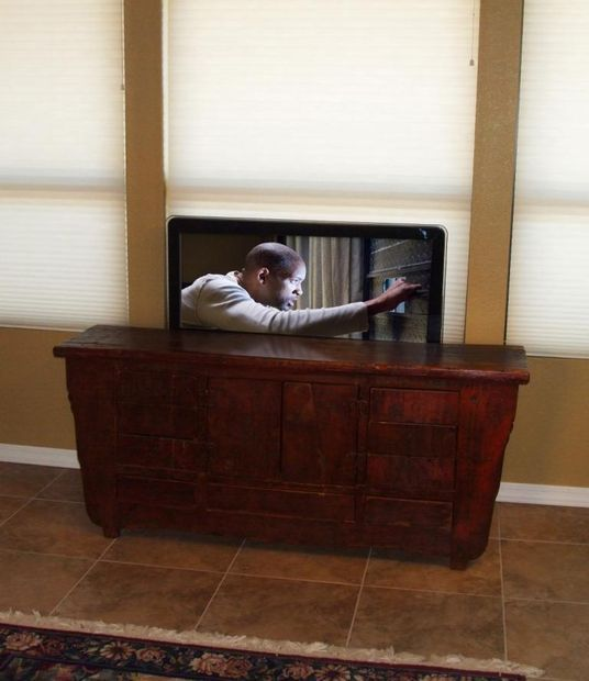 tv with pop up tv lift mounted behind furniture