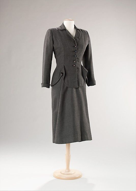 """Suit, Jean Dessès (French, born Egypt, 1904–1970), manufactured by I.M. Bagedonow: 1953, French, wool.     """"This suit from 1953 is unique, most notably in the construction of the skirt. The draping of the front panel is consistent with the designer's technique and is typical of the period. While the suit is well-tailored to the silhouette, the draping at the front panel adds emphasis to the waist."""""""
