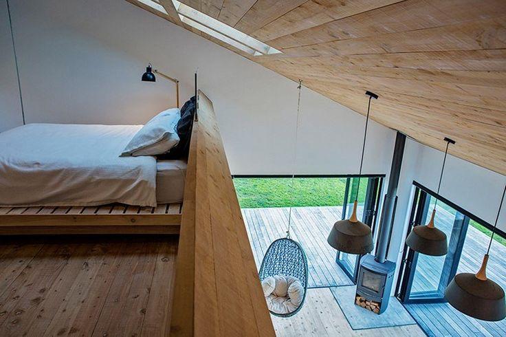 La chambre principale se trouve sous un toit en pente et le long bureau de travail en bois la transforme en un bureau. Et quoi de mieux que de travailler chez vous?