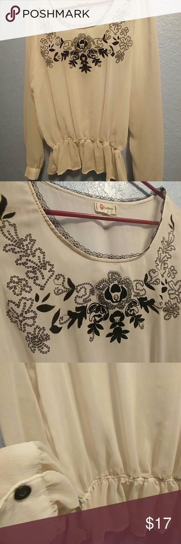 Pretty Sheer Top Sheer cream long sleeve top with black designs on the chest and lace on the neckline. Scrunch around the waist with some flow below. Black buttons on the cuffs located on each arm. Great lighly worn condition. Size medium Tops Blouses