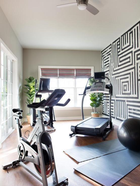 Amazing home gym and yoga room boasts a black and white graphic hand painted wall alongside NordicTrack gym equipment and yoga mats atop a wood like floor.