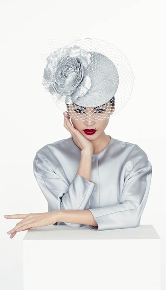 Ice blue headpiece/hat by Philip Treacy, Model: Gemma Chan,   Jacket by Giorgio Armani, Make-up: Topolino.