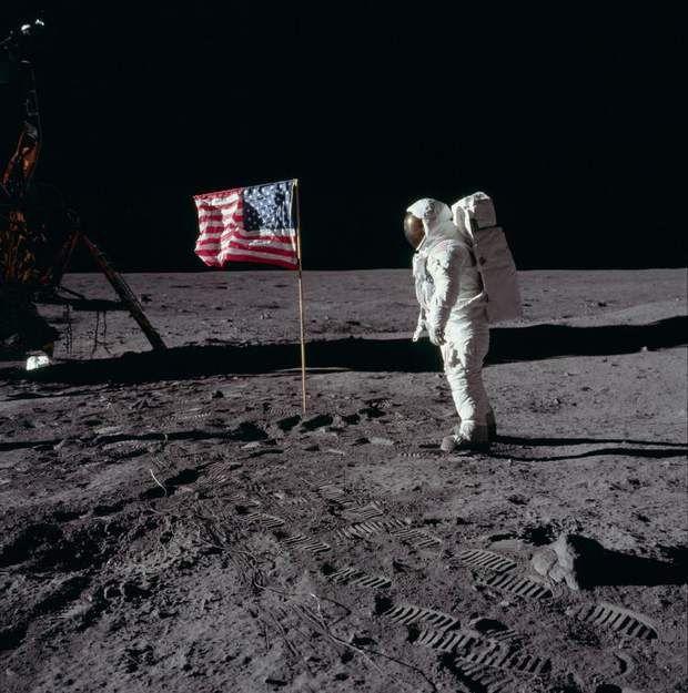 """Face-à-faceEdwin """"Buzz"""" Aldrin pose avec le drapeau américain. Si vous regardez attentivement, vous pourrez apercevoir le visage de Aldrin à travers la visière de son casque."""