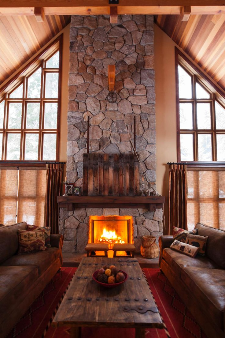 Hidden TV--A towering stone fireplace draws you into this lodge-style living room. Leather sofas are topped with Southwestern pillows, while a clever pulley system above the mantel conceals the TV behind a reclaimed wood screen.