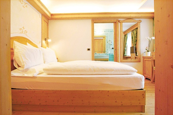 Suite Le Cort. 2 eleganti camere comunicanti. Pavimento in legno naturale.    DOTATE DI:  Stanza 1:  - letto matrimoniale  - telefono, TVColor e cassaforte  - ampio bagno con doppio lavandino, phon    Stanza 2:  - salottino (oppure 1/2 letti aggiunti)  - TVColor con Play-Station e WI-FI  - secondo bagno con doccia, phon  - minibar  - ampie finestre.