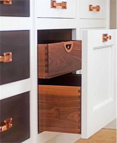 Custom kitchen cabinetry from Christopher Peacock features dovetail joints, white inset cabinet faces and highly polished pulls and nobs in copper.